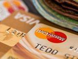 Forskellige kreditkort ligger på bord med penge