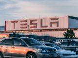 Tesla bygning med en masse parkerede biler foran
