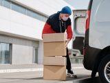 Mand pakker baggagerummet af hans bil